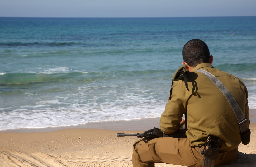 An IDF soldier sits on a beach in Tel Aviv (photo credit: MARC ISRAEL SELLEM/THE JERUSALEM POST)