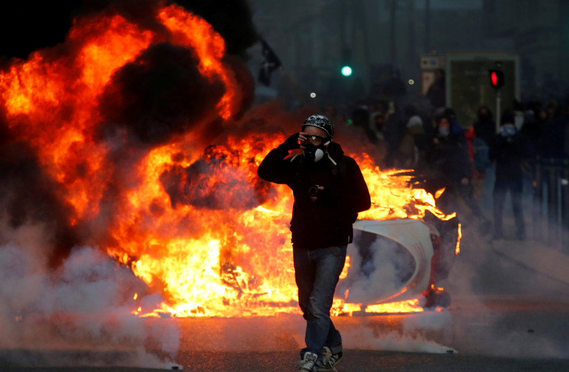 """A car burns during clashes with police at a demonstration of the """"yellow vests"""" movement in Marseille, France, December 8, 2018 (photo credit: JEAN-PAUL PELISSIER / REUTERS)"""