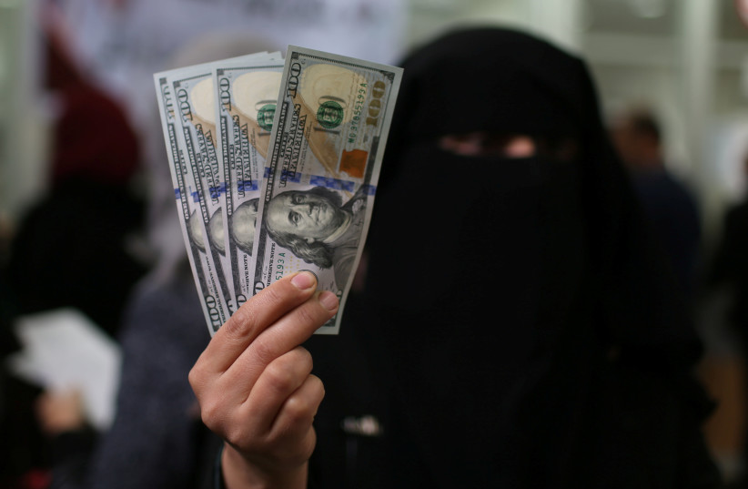 A Palestinian Hamas-hired civil servant displays U.S. Dollar banknotes after receiving her salary paid by Qatar, in Khan Younis in the southern Gaza Strip December 7, 2018 (photo credit: IBRAHEEM ABU MUSTAFA / REUTERS)