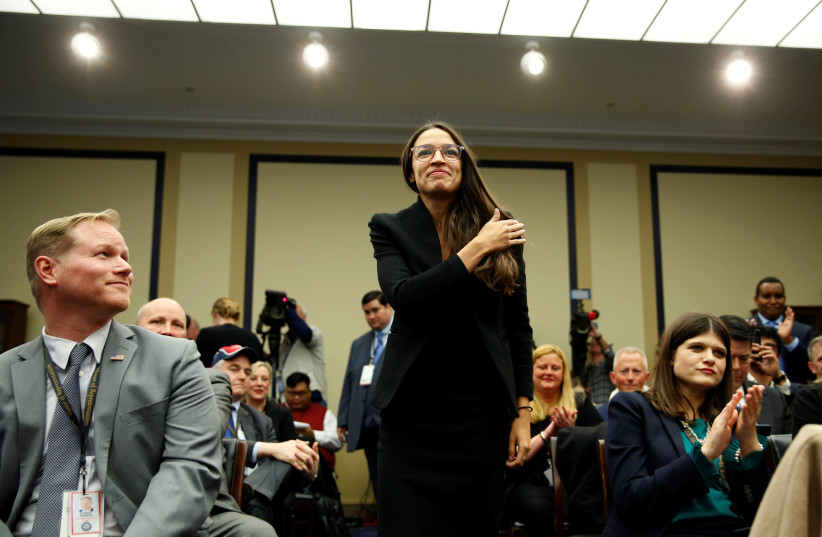 Representative-elect Alexandria Ocasio Cortez (D-NY) crosses her self before drawing 40 during a lottery for office assignments on Capitol Hill in Washington, U.S., November 30, 2018 (photo credit: REUTERS/JOSHUA ROBERTS)