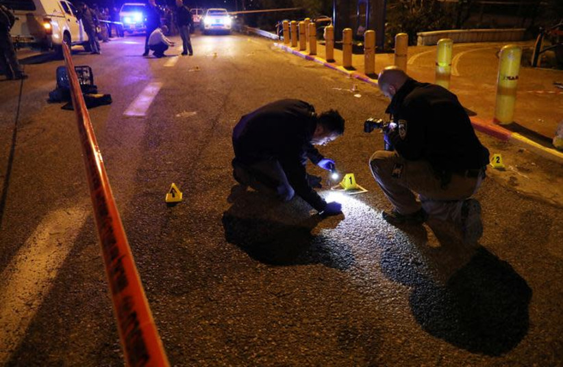 Israeli security forces and emergency personnel work at the scene of shooting attack, near the Israeli settlement of Ofra, December 9, 2018 (photo credit: AMMAR AWAD / REUTERS)