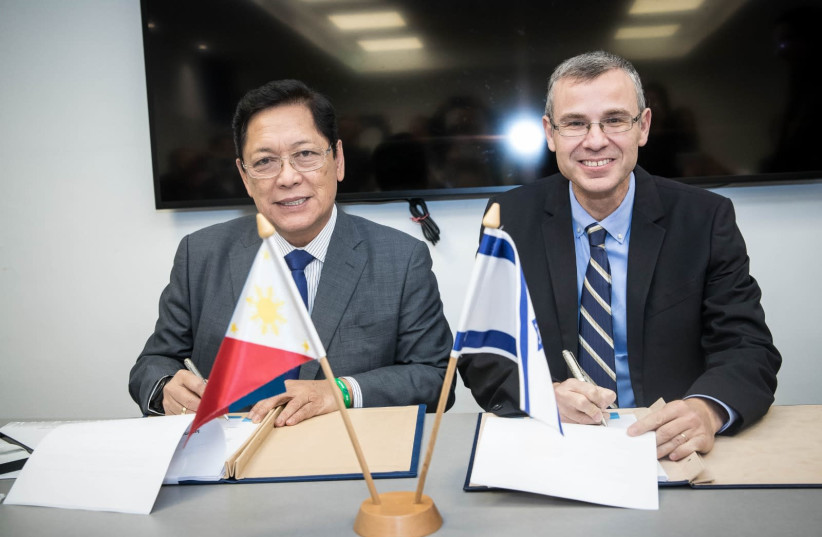 Minister of Tourism Yariv Levin (R) and Philippines Labor and Employment Minister Silvestre Bello sign a bilateral labor agreement, December 11, 2018  (photo credit: ODED KARNI)