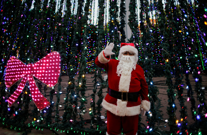 A man dressed as Santa Claus gestures in front of a Christmas tree (photo credit: OSWALDO RIVAS/REUTERS)