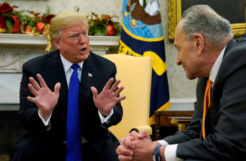 U.S. President Donald Trump speaks to Senate Minority Leader Chuck Schumer (D-NY) during a meeting with the House and Senate Democratic leadership in the Oval Office of the White House in Washington, U.S., December 11, 2018 (photo credit: KEVIN LAMARQUE/REUTERS)