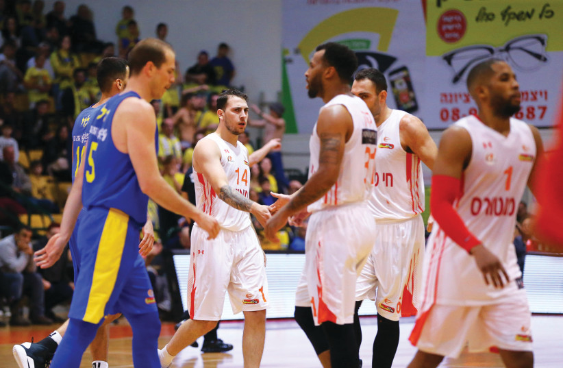 Ironi Ness Ziona players (in white) celebrate their 83-81 victory over Maccabi Tel Aviv in Basketball Super League action this week (photo credit: ERAN LUF)