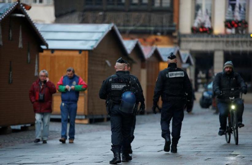 French Gendarmes patrol past wooden barracks shops at the traditional Christkindelsmaerik (Christ Child market) closed the day after a shooting in Strasbourg, France, December 12, 2018. (photo credit: VINCENT KESSLER/ REUTERS)