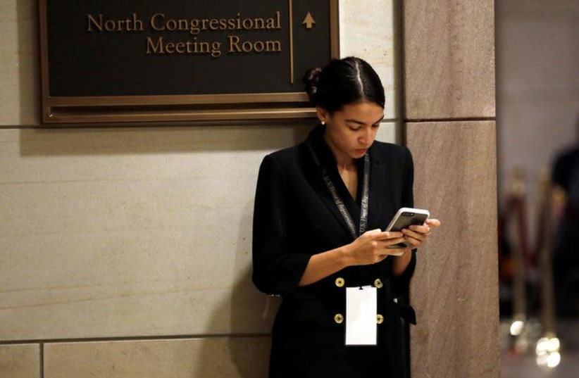 Alexandria Ocasio-Cortez waits for a House of Representatives member-elect welcome briefing on Capitol Hill in Washington, U.S., November 15, 2018 (photo credit: YURI GRIPAS/REUTERS)