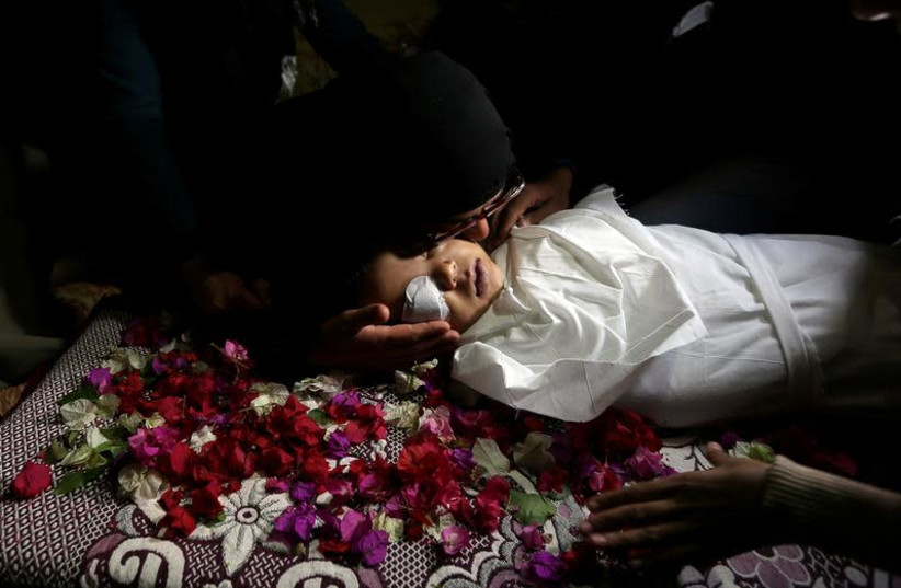 VISUAL COVERAGE OF SCENES OF INJURY OR DEATH A relative kisses the body of Palestinian boy Ahmed Abed during his funeral in Khan Younis in the southern Gaza Strip December 12, 2018.  (photo credit: REUTERS/IBRAHEEM ABU MUSTAFA)