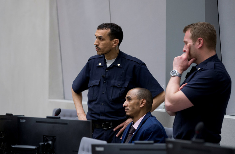Alleged jihadist leader Al Hassan Ag Abdoul Aziz Ag Mohamed Ag Mahmoud (2ndR), listens to his duty counsel Yasser Hassan (L), prior to his initial appearance on charges of war crimes and crimes against humanity at the International Criminal Court in The Hague, The Netherlands April 4, 2018 (photo credit: PETER DEJONG/REUTERS)