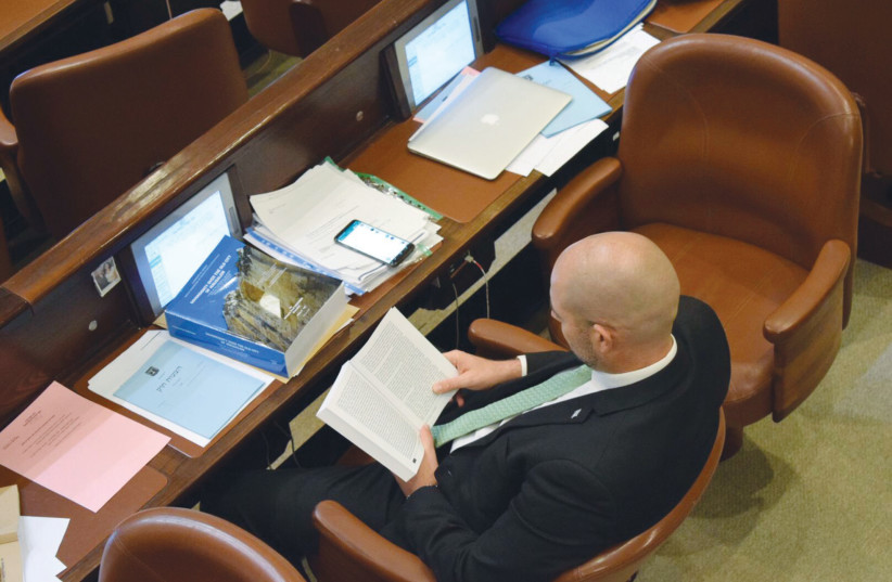 Likud MK Amir Ohana reads during a debate in the Knesset plenum  (photo credit: Courtesy)