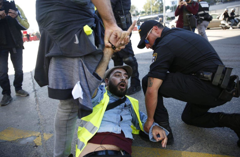 """A demonstrator is arrested at a """"Yellow Vest"""" protest in Tel Aviv, December 14, 2018 (photo credit: YELLOW VEST PROTEST HEADQUARTERS IN ISRAEL)"""