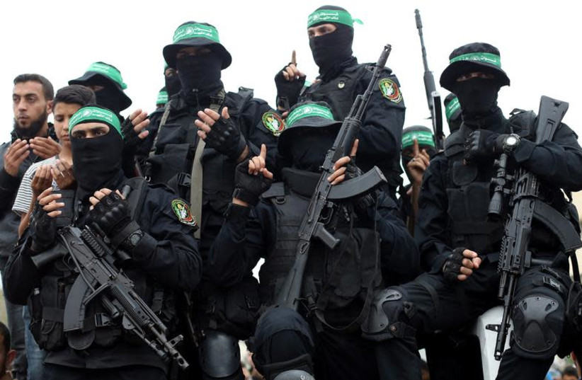 Palestinian Hamas militants attend the funeral of their comrades who were killed in an explosion, in the central Gaza Strip May 6, 2018 (photo credit: REUTERS/IBRAHEEM ABU MUSTAFA)