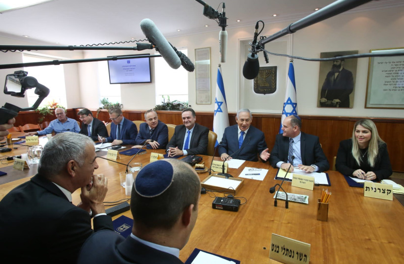 Naftali Bennett (foreground) looks on as Prime Minister Benjamin Netanyahu (C) addresses a weekly cabinet meeting, December 16th, 2018 (photo credit: MARC ISRAEL SELLEM/THE JERUSALEM POST)