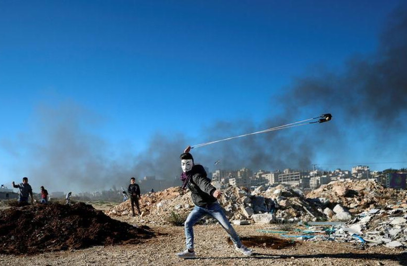 A Palestinian uses a sling to hurl stones during clashes with Israeli troops near the Jewish settlement of Beit El, near Ramallah, in the Israeli-occupied West Bank December 14, 2018.  (photo credit: REUTERS/MOHAMAD TOROKMAN)