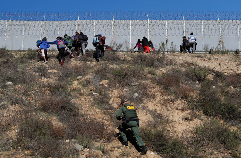 U.S. Customs and Border Protection (CBP) officials detain a group of migrants, part of a caravan of thousands from Central America trying to reach the United States, after they crossed illegally from Mexico to the U.S, as seen from Tijuana, Mexico, December 15, 2018. (photo credit: CARLOS GARCIA RAWLINS/ REUTERS)