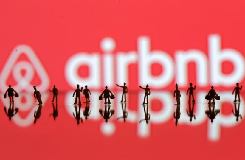 A 3D printed people's models are seen in front of a displayed Airbnb logo in this illustration taken, June 8, 2016 (photo credit: DADO RUVIC/REUTERS)