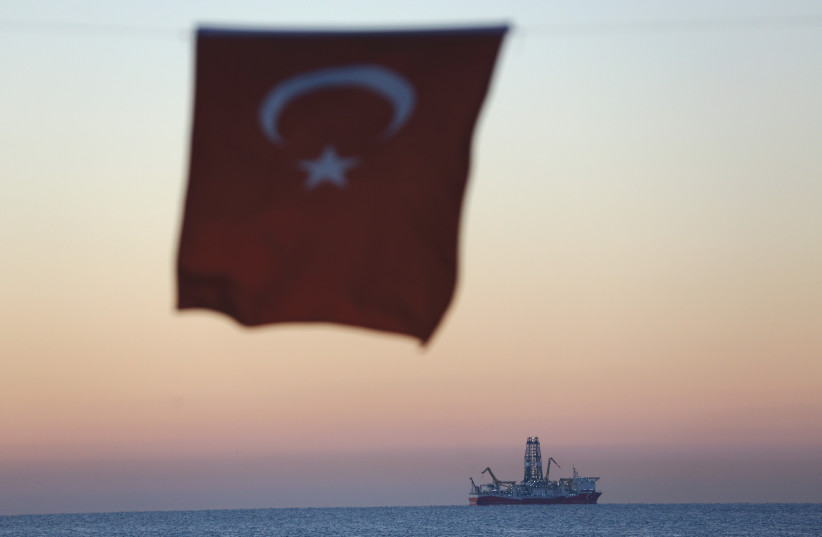 A TURKISH national flag hangs in the foreground as drilling vessel 'Fatih' is seen off the Mediterranean resort city of Antalya, Turkey, in October (photo credit: REUTERS)