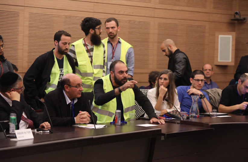 'Yellow vest' protesters in the Israeli Knesset, including David Mizrahi (seated, in vest) and Orly Bar Lev (seated, r.), December 18, 2018  (photo credit: KNESSET SPOKESPERSON'S OFFICE)