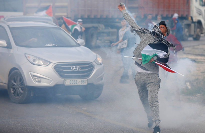 A Palestinian demonstrator returns a tear gas canister fired by Israeli troops during clashes at the Hawara checkpoint near Nablus, December 2, 2018 (photo credit: MOHAMAD TOROKMAN/REUTERS)