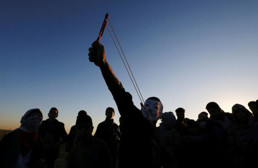 A Palestinian demonstrator uses a slingshot to hurl stones at Israeli troops during a protest at the Israel-Gaza border fence, in the southern Gaza Strip December 14, 2018. (photo credit: IBRAHEEM ABU MUSTAFA / REUTERS)