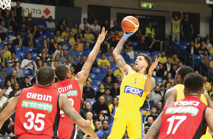 Maccabi Tel Aviv's Scottie Wilbekin shoots over the Hapoel Jerusalem defense for two of his 20 points in Maccabi's 91-78 home victory over Hapoel in Basketball Super League action this week (photo credit: ERAN LUF)