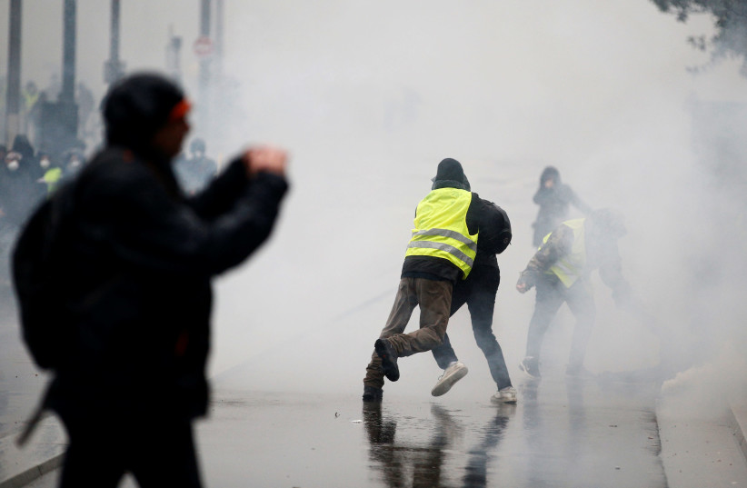 """A man wearing a yellow vest tackles a protester as tear gas floats in the air during clashes with police at a demonstration by the """"yellow vests"""" movement in Nantes, France, December 15, 2018 (photo credit: STEPHANE MAHE / REUTERS)"""