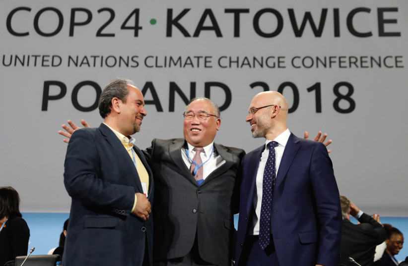 (FROM LEFT) Iran's head of delegation Majid Shafiepour Motlagh, China's head of delegation Xie Zhenhua and COP24 president Michal Kurtyka smile after adopting the final agreement during the COP24 UN Climate Change Conference 2018 in Katowice, Poland, on December 15. (photo credit: REUTERS)