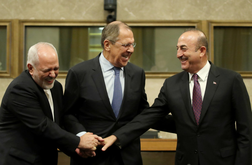 Russian Foreign Minister Sergei Lavrov, Turkish Foreign Minister Mevlut Cavusoglu and Iranian Foreign Minister Mohammad Javad Zarif shake hands as they attend a news conference after talks on forming a constitutional committee in Syria, at the United Nations in Geneva, Switzerland, December 18, 2018 (photo credit: REUTERS/DENIS BALIBOUSE)