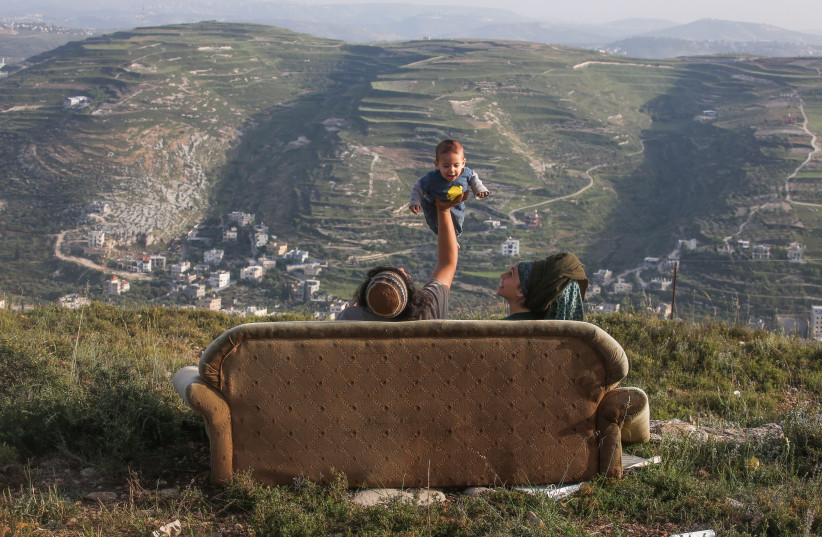 Miriam (R) and Neryah (L) look up at their baby in a settlement (photo credit: MARC ISRAEL SELLEM/THE JERUSALEM POST)
