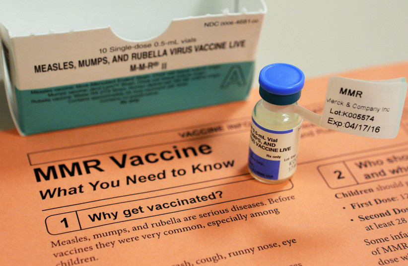 A vial of measles, mumps and rubella vaccine and an information sheet is seen at a hospital (photo credit: REUTERS/BRIAN SNYDER)