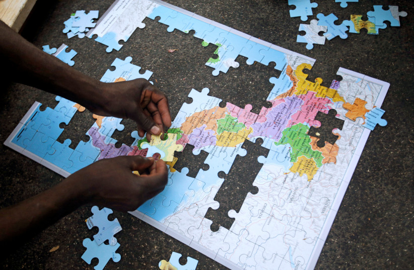 Migrants assemble a puzzle depicting Italy on a map, at a makeshift camp in Via Cupa (Gloomy Street) in downtown Rome, Italy, August 2, 2016 (photo credit: REUTERS/MAX ROSSI)