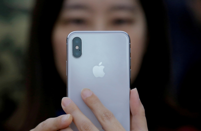 An attendee uses a new iPhone X during a presentation for the media in Beijing, China October 31, 2017. (photo credit: REUTERS/THOMAS PETER)