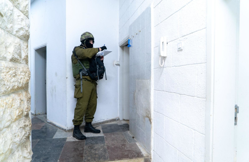 An IDF soldier maps out the home of the Barghouti brother terrorists  (photo credit: IDF SPOKESPERSON'S UNIT)