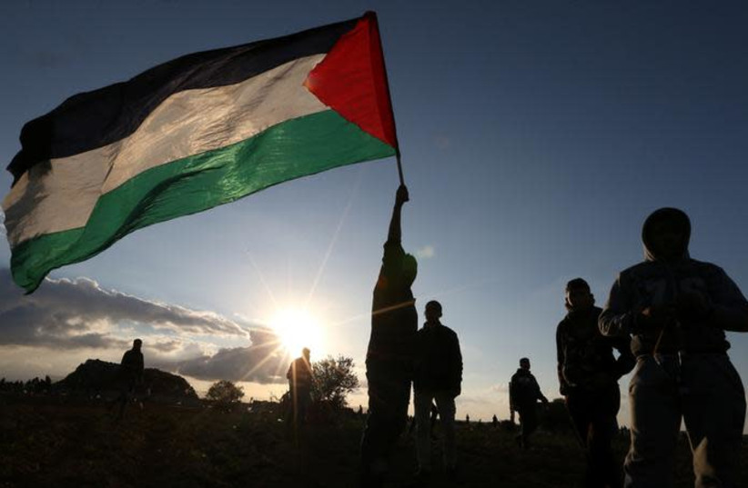 A demonstrator holds a Palestinian flag during a protest near the Israel-Gaza border fence, in the southern Gaza Strip December 21, 2018. (photo credit: REUTERS/IBRAHEEM ABU MUSTAFA)