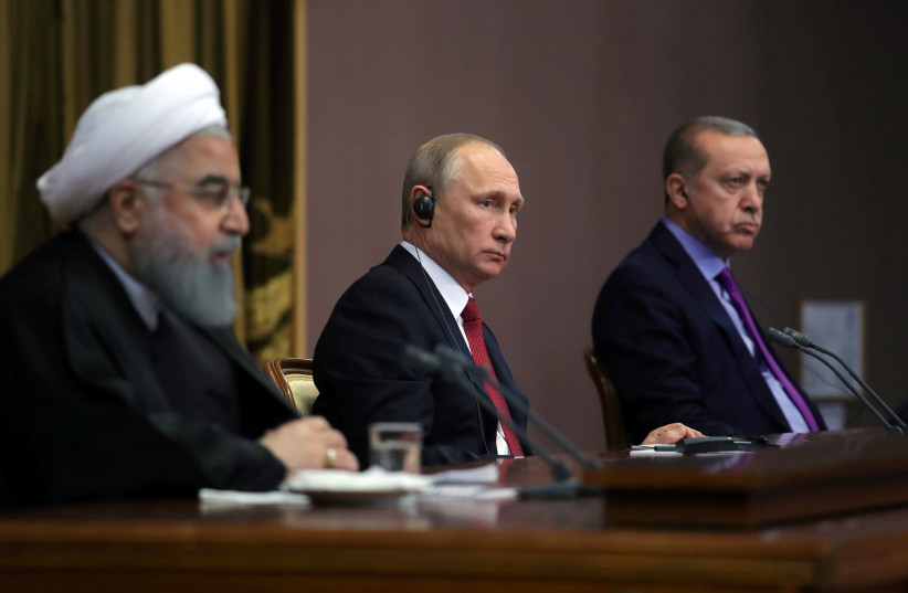 Iran's President Hassan Rouhani together with his counterparts, Russia's Vladimir Putin and Turkey's Tayyip Erdogan, attend a joint news conference following their meeting in Sochi, Russia November 22, 2017 (photo credit: SPUTNIK/MIKHAIL KLIMENTYEV/KREMLIN VIA REUTERS)