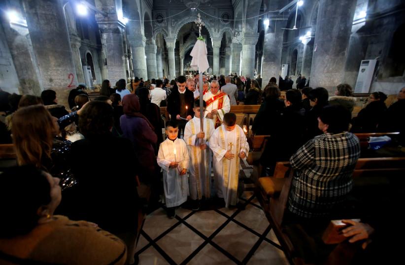 Iraqi Christians attend a mass on Christmas Eve at the Grand Immaculate Church in Qaraqosh (al-Hamdaniya), near Mosul (photo credit: THAIER AL-SUDANI/REUTERS)