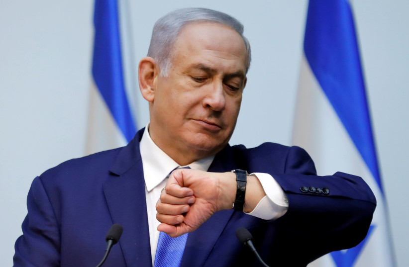 Israeli Prime Minister Benjamin Netanyahu looks at his watch before delivering a statement at the Knesset, Israel's parliament, in Jerusalem December 19, 2018 (photo credit: AMIR COHEN/REUTERS)