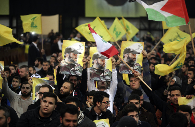Supporters of Lebanon's Hezbollah leader Sayyed Hassan Nasrallah carry pictures of Hezbollah's late military leader Imad Moughniyah as Nasrallah appears on a screen to speak at an event to commemorate the deaths of six Hezbollah fighters and an Iranian general killed by an Israeli air strike in Syri (photo credit: REUTERS/KHALIL HASSAN)