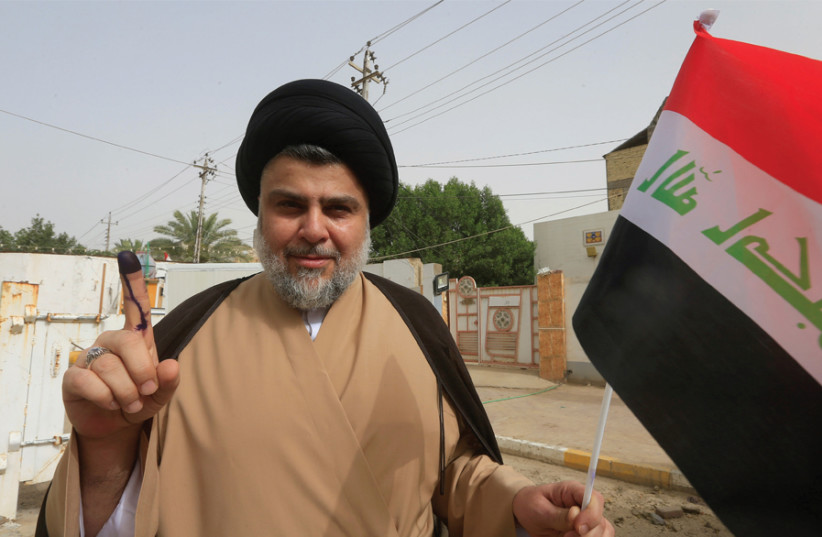IRAQI SHI'ITE cleric Muqtada al-Sadr shows his ink-stained finger after casting his vote at a polling station during the parliamentary election in Najaf, Iraq, on May 12. (photo credit: REUTERS)