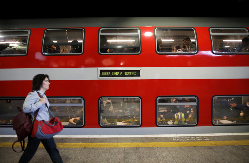 A woman walks on a platform in front of a train as passengers are seen through the carriage windows at Tel Aviv's HaShalom train station, Israel November 25, 2018. Picture taken November 25, 2018 (photo credit: REUTERS/CORINNA KERN)