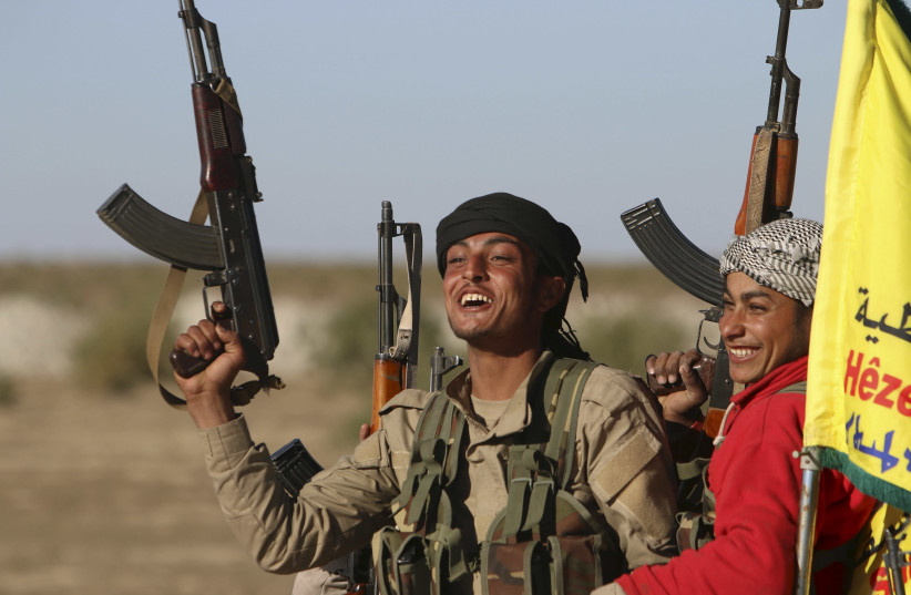 Fighters from the Democratic Forces of Syria carry their weapons as they cheer near the Syrian town of al Houl in Hasaka province, after they took control of the area, November 14, 2015. A U.S.-backed Syrian rebel alliance on Friday captured the town of al Houl in Hasaka province, which had been hel (photo credit: REUTERS/RODI SAID)