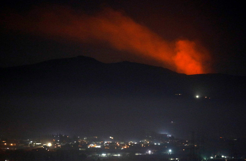 Smoke rises past a mountain as seen from Damascus countryside, Syria December 25, 2018 (photo credit: OMAR SANADIKI/REUTERS)