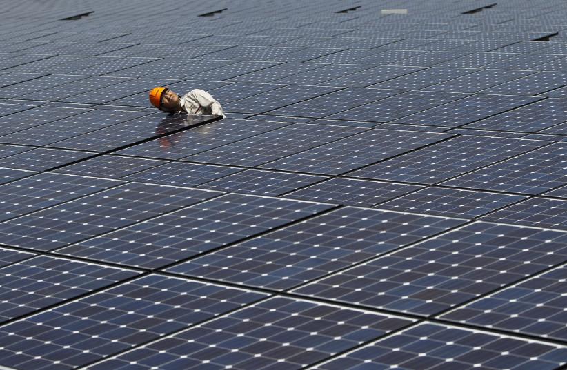 A worker checks solar panels at a solar power field in Kawasaki, near Tokyo July 6, 2011 (photo credit: TORU HANAI / REUTERS)