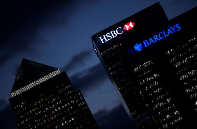 HSBC and Barclay's buildings are lit up at dusk in the Canary Wharf financial district of London, Britain, November 19, 2018 (photo credit: TOBY MELVILLE/REUTERS)