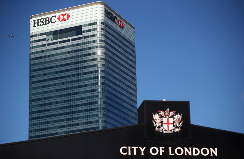 Barclays' building in Canary Wharf is seen behind a City of London sign outside Billingsgate Market in London. (photo credit: REUTERS)