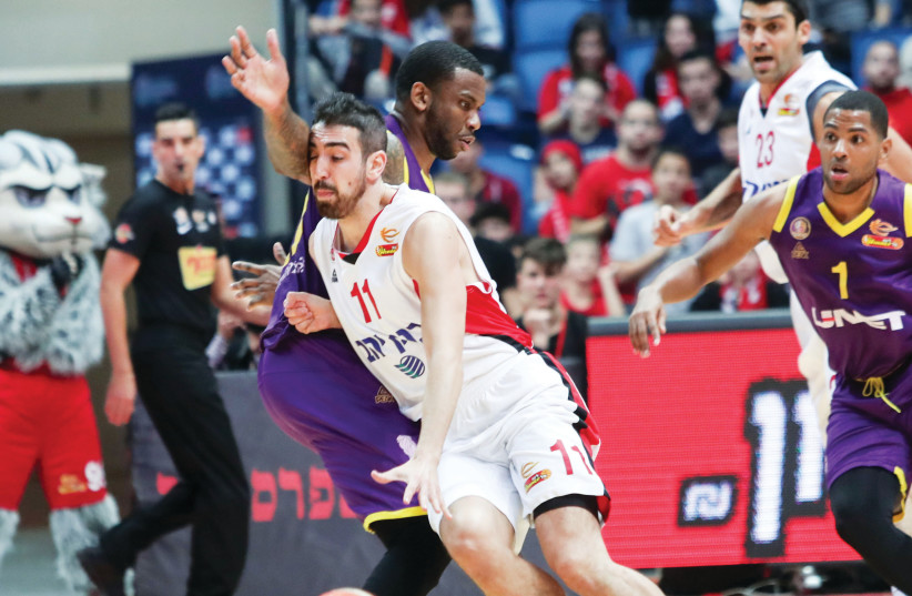 Hapoel Jerusalem's Bar Timor drives to the basket against the Hapoel Holon defense during the Reds' 94-74 home victory over Holon in Basketball Super League action this week (photo credit: DANNY MARON)
