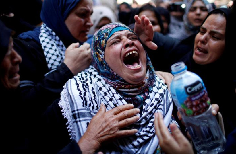 A relative mourns during the funeral of Palestinian nurse Razan Al-Najar, who according to health officials and a witness was killed by Israeli forces as she tried to help a wounded protester at the Gaza border, in Khan Younis in the southern Gaza Strip June 2, 2018. (photo credit: REUTERS/MOHAMMED SALEM)