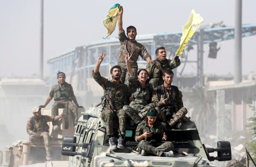 Kurdish-led militiamen ride atop military vehicles as they celebrate victory over Islamic State in Raqqa, Syria, October 17, 2017 (photo credit: REUTERS/ERIK DE CASTRO)