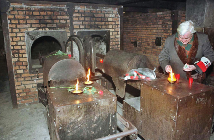 A Holocaust survivor lights a candle at an Auschwitz crematorium (photo credit: REUTERS)