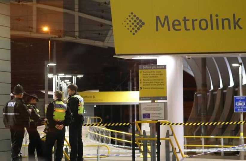 Police officers stand at the end of a tram platform following a stabbing at Victoria Station in Manchester, Britain, January 1, 2019 (photo credit: PHIL NOBLE/REUTERS)